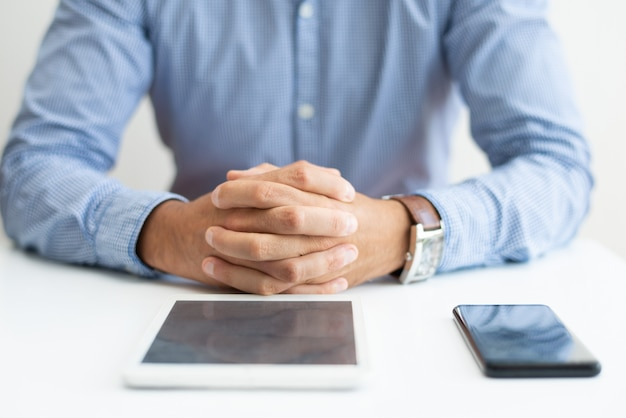 Primo piano di uomo seduto alla scrivania con tablet e smartphone