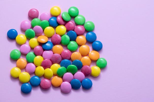 Primo piano di uova di cioccolato e caramelle scende sul tavolo rosa