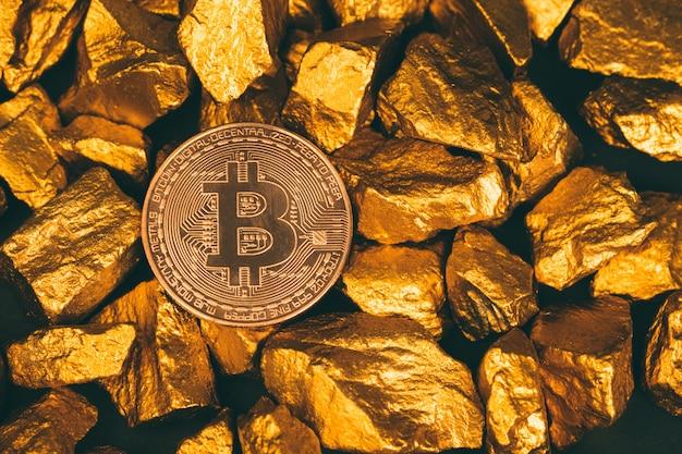 Primo piano di valuta digitale bitcoin e pepita d'oro o minerale d'oro su sfondo nero, pietra preziosa o grumo di pietra dorata