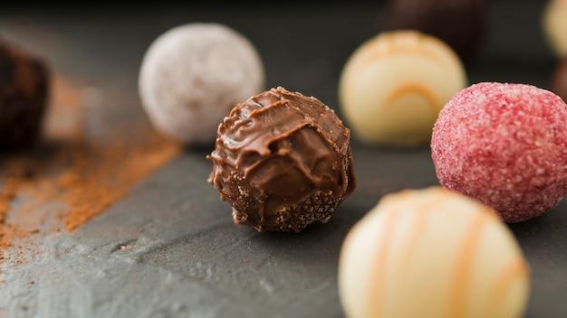 Primo piano di vari cioccolatini rotondi sul tavolo nero
