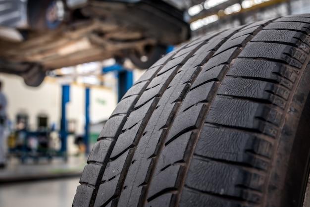 Primo piano di vecchi pneumatici con pneumatici grandi, danneggiati e incrinati su pneumatici neri