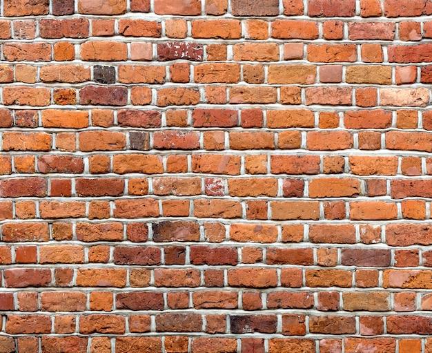 Primo piano di vecchio muro di mattoni solido non intonacato marrone rosso stagionato d'annata naturale.