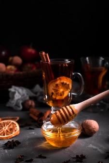 Primo piano di versamento di miele e tè