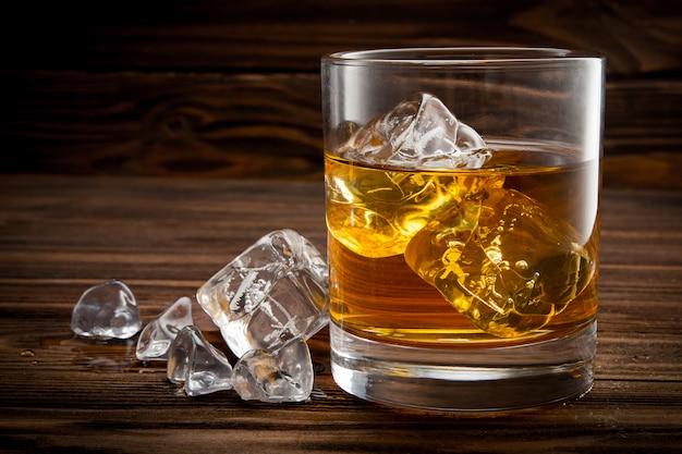 Primo piano di vetro con ghiaccio e whisky