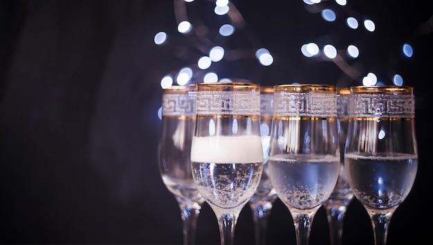 Primo piano di vetro trasparente con champagne contro il fondo scuro del bokeh