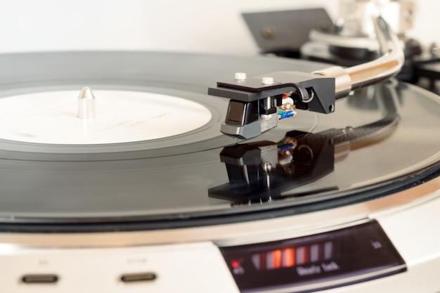 Primo piano di vinile turntablã'⃠in azione, ago su disco in vinile, primo piano della cartuccia di guscio testa hi-fi nera, braccio alla piastra, spazio di copia