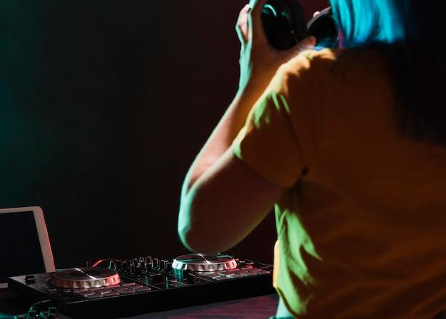 Primo piano dj femminile che controlla suono