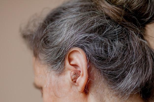 Primo piano donna senior inserendo apparecchio acustico nelle sue orecchie