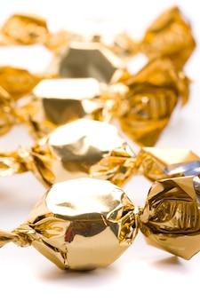 Primo piano dorato dei dolci su fondo bianco