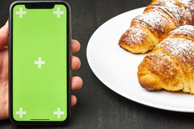Primo piano equipaggia la mano con uno smartphone con una chiave cromata dello schermo verde e croissant su una superficie nera. cornetti con zucchero in polvere su un piatto.