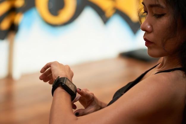 Primo piano estremo della sportiva asiatica che controlla impulso con l'apparecchio elettronico