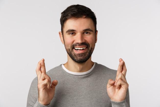 Primo piano fiducioso e allegro, ottimista ragazzo adulto con la barba in maglione grigio, credi che il miracolo accada, speri che il sogno diventi realtà, incrocia le dita buona fortuna, pregando o assapora l'affare è andato bene