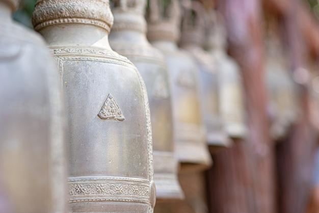 Primo piano foderato con bellissime campane. campana dorata antica di fede in tempio di buddha o posto in tailandia. campane d'ottone stagionate voluminose che appendono in una fila in tempio buddista tailandese fuori. calma e credi.