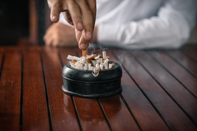 Primo piano giovane ragazzo in una camicia bianca, tiene una sigaretta tra le mani e la macina in un posacenere pieno di sigarette