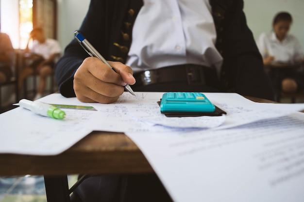 Primo piano gli studenti che scrivono e leggono gli fogli di risposta degli esami di esercitazione in aula della scuola con lo stress.
