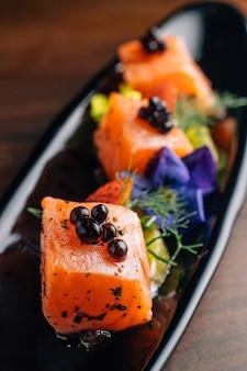 Primo piano griglia di salmone raro di media e grassa con caviale.