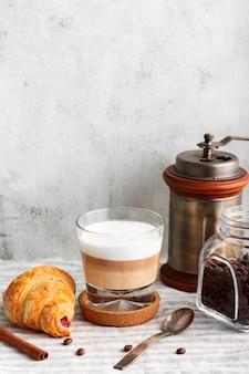 Primo piano gustoso caffè con latte e cornetto