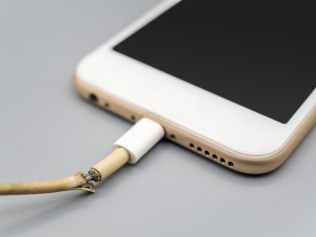 Primo piano il cavo del caricabatterie dello smartphone danneggiato