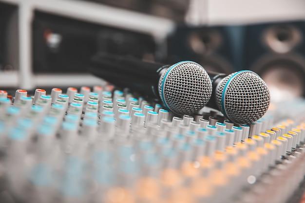 Primo piano, il microfono è collocato sul mixer audio professionale dello studio per vivere il concetto di produzione di apparecchiature multimediali e audio.