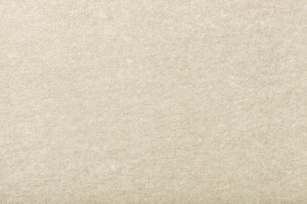 Primo piano in tessuto scamosciato opaco beige chiaro. texture vellutata di feltro.