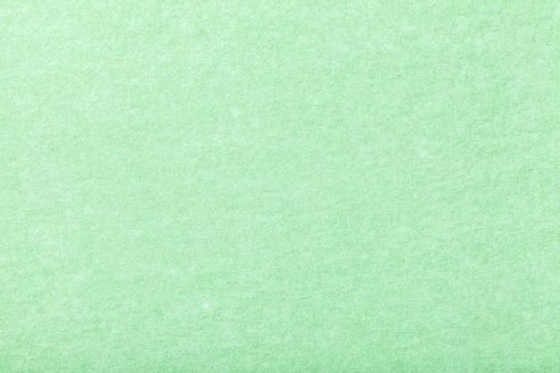 Primo piano in tessuto scamosciato opaco verde chiaro. texture vellutata di feltro.