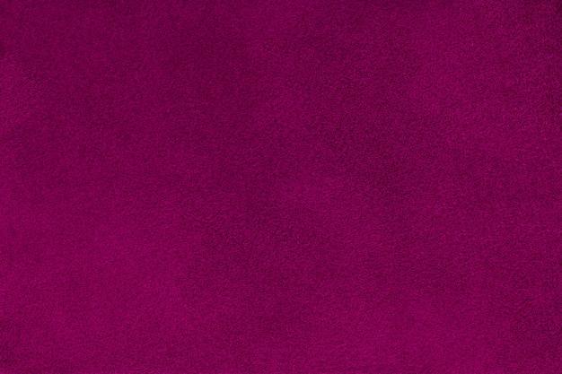 Primo piano in tessuto scamosciato opaco viola scuro. trama di velluto.