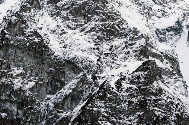 Primo piano innevato della montagna. la trama delle pietre nella neve