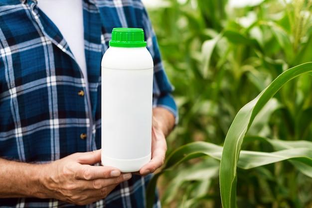 Primo piano la bottiglia con fertilizzanti chimici nelle mani maschili del contadino - immagine