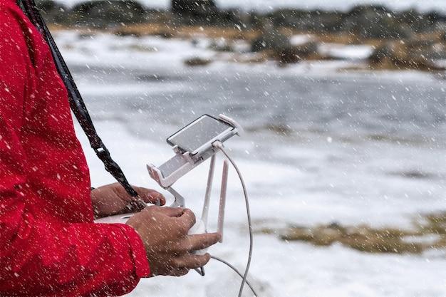 Primo piano la mano del fotografo che controlla il drone sopra seascape