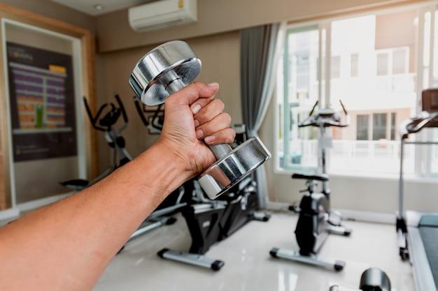 Primo piano la mano di un uomo tiene un manubrio con la mano sinistra in palestra, concetto per l'esercizio e l'assistenza sanitaria.