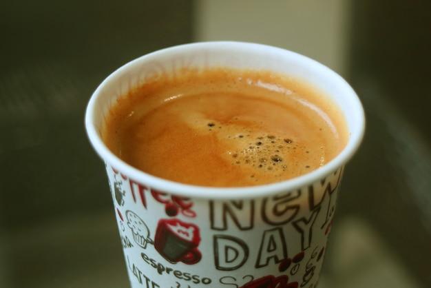Primo piano la trama della superficie del caffè caldo in una tazza di carta
