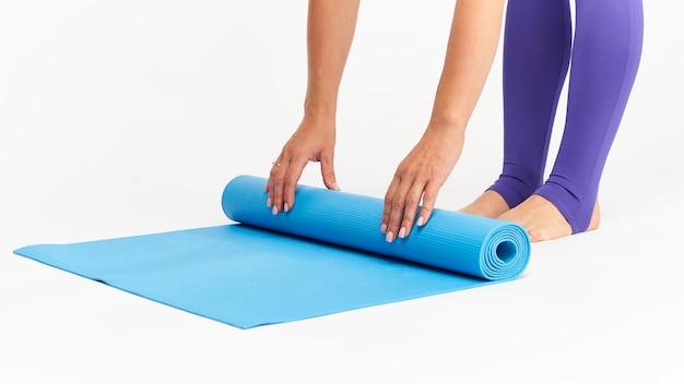 Primo piano mani e piedi della donna in abbigliamento sportivo, stendere stuoia per lo sport.