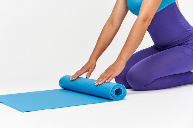 Primo piano mani e piedi di una donna in abbigliamento sportivo, stendere un tappetino per lo sport