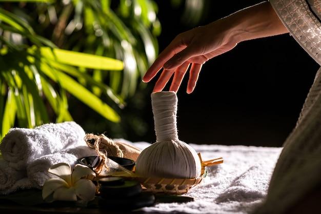 Primo piano: mani femminili in possesso di palla di erbe caldo per massaggio tailandese
