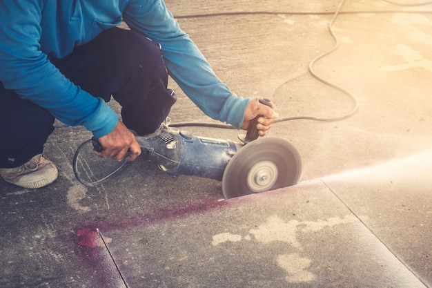 Primo piano mano che taglia pavimento in calcestruzzo con macchina.