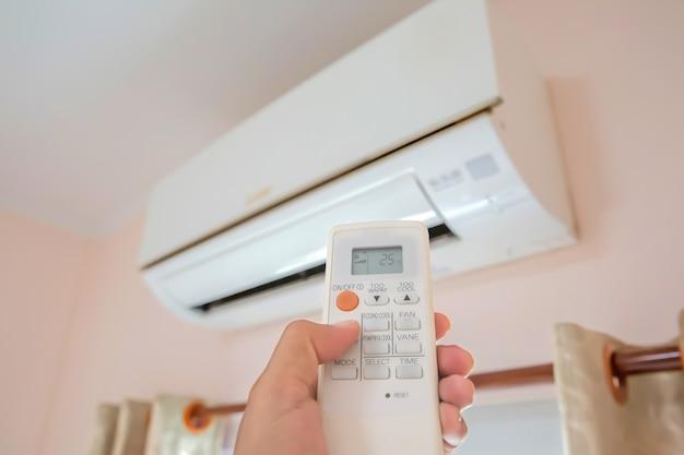 Primo piano mano e telecomando aria condizionata impostata a 25 gradi di temperatura.