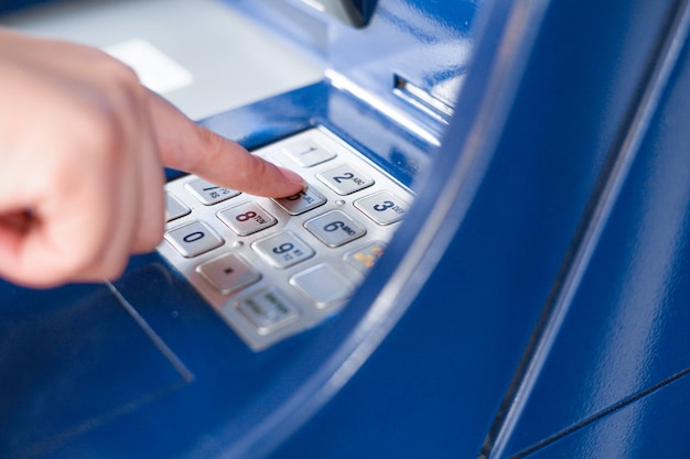 Primo piano mano inserendo pin o password presso un bancomat