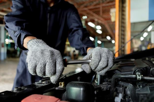 Primo piano, meccanico automatico le persone riparano un'auto usa una chiave inglese e un cacciavite per lavorare. servizio di riparazione. autentico primo piano.