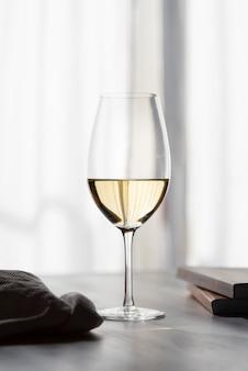 Primo piano mezzo vuoto di vetro di vino bianco