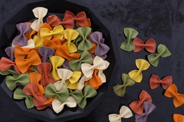 Primo piano multicolore crudo italiano della pasta del farfalle su fondo nero.