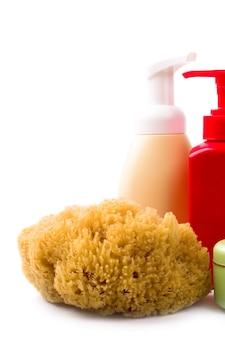Primo piano naturale dei cosmetici e della spugna su fondo bianco