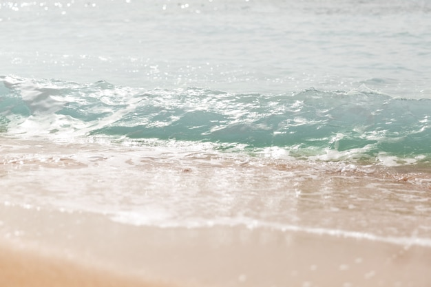 Primo piano onde del mare con spruzzi sulla spiaggia di sabbia. avvicinamento