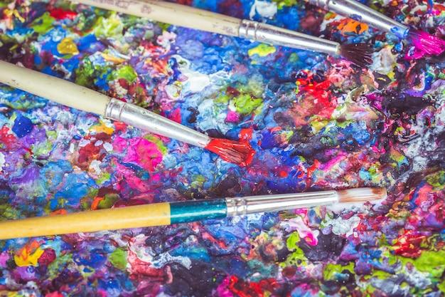 Primo piano pennello sul vassoio con macchia di vernice colorata sulla superficie
