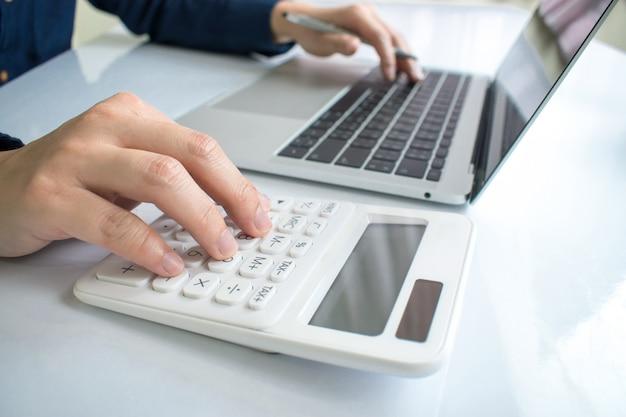 Primo piano per le mani degli uomini d'affari, sta seriamente calcolando il grafico finanziario sul portatile.