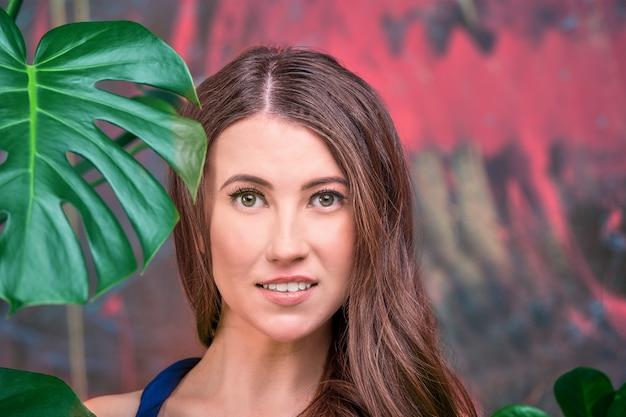 Primo piano portraita giovane donna bruna, che indossa un abito blu.