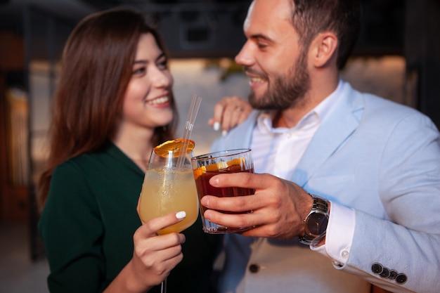 Primo piano potato dei bicchieri di cocktail tintinnanti di una coppia amorosa felice, celebrante il giorno di biglietti di s. valentino al bar