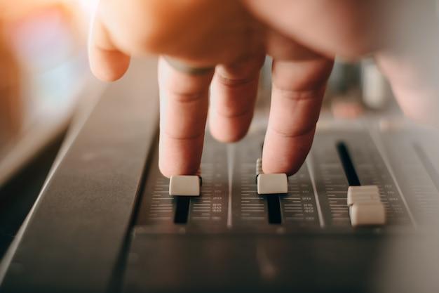 Primo piano professionale del miscelatore del suono della fase alla mano dell'ingegnere del suono facendo uso del cursore dell'audio mix che funziona durante l'esibizione di concerto. dj sta regolando il volume del suono