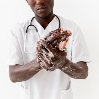 Primo piano professionale delle mani di lavaggio di giovane medico