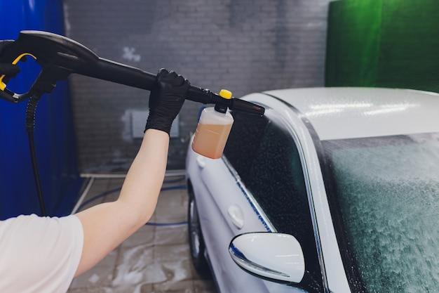 Primo piano pulizia auto con acqua ad alta pressione, idropulitrice ad alta pressione in corso di lavaggio auto.