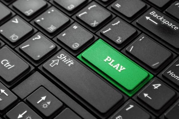 Primo piano pulsante verde con la parola play, su una tastiera nera. sfondo creativo, copia spazio. concetto di pulsante magico, intrattenimento, tempo libero.